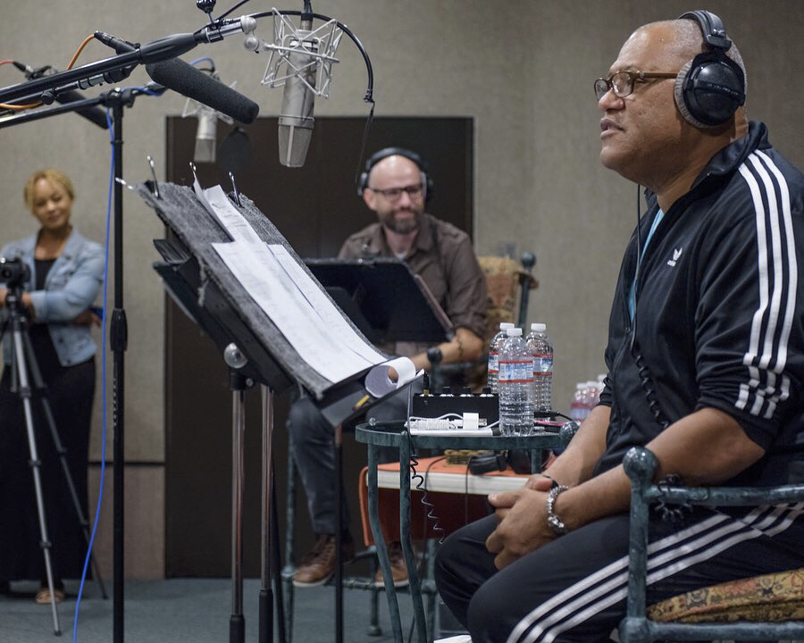 "Laurence Fishburne sits at a microphone, recording ""Bronzeville"" from a script, as K.C. Wayland and another crew member look on"